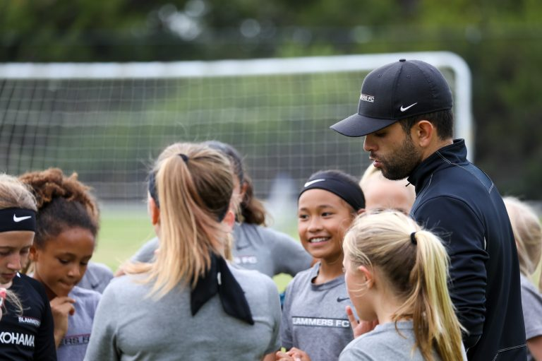huddle of girls soccer players with Coach Pete Aguirre