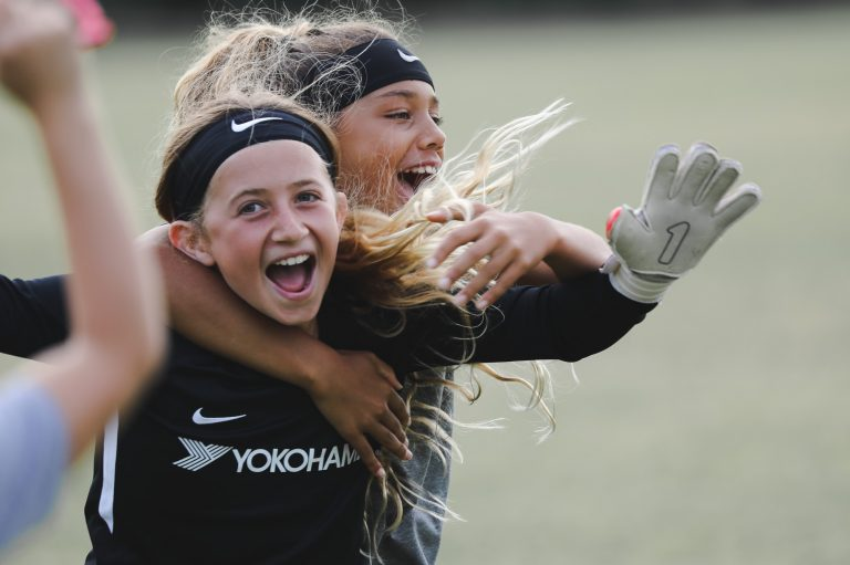 goalkeeper and field player smiling and laughing